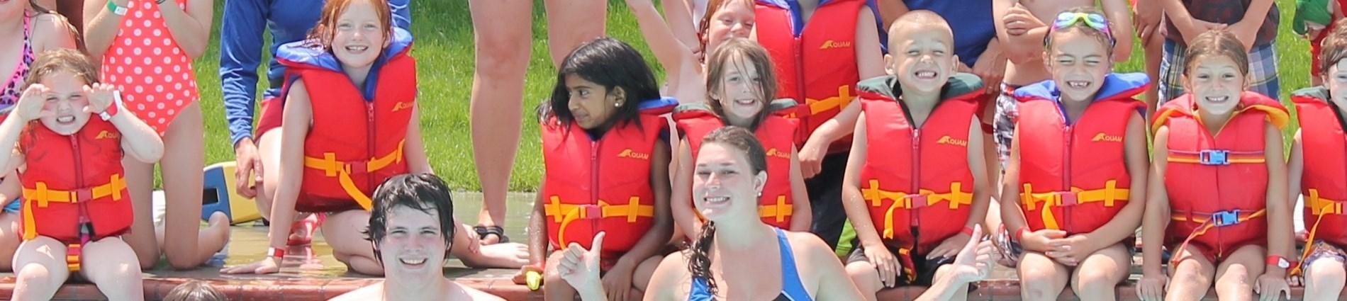 kids in lifejackets in pool