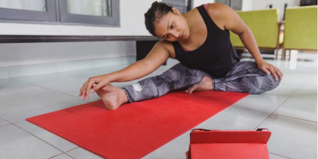 woman on mat exercising to ipad